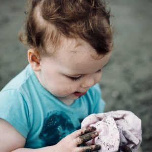 toddler with dirt on hands and clothes