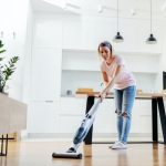 woman cleaning linoleum floor with an electric steam mop and white cabinetry