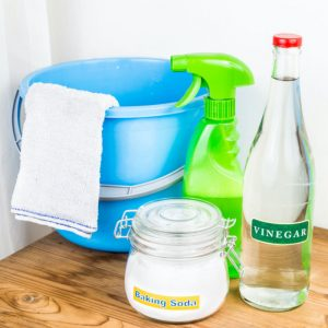 glass jars of baking soda and vinegar with cleaning supplies including a bucket and towel