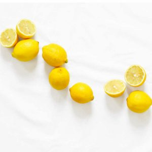 several lemons on a white background to be combined with white distilled vinegar