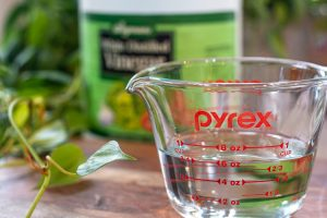 pyrex measuring cup with hot water and a bottle of white distilled vinegar in the background for adding to a load of musty smelling towels