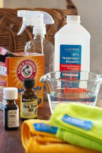 alcohol, baking soda, essential oils and microfiber cloths on a table